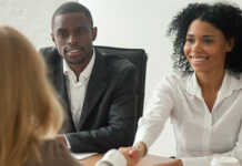 A new hire smiling while shaking an HR representative's hand.